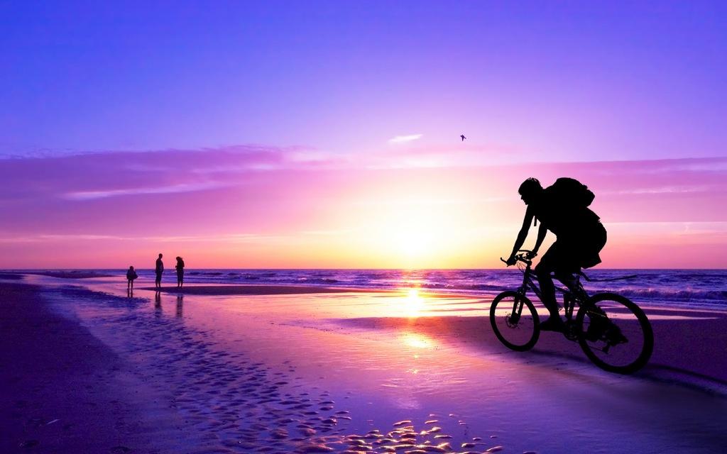 Montando Bicicleta En La Playa Al Atardecer