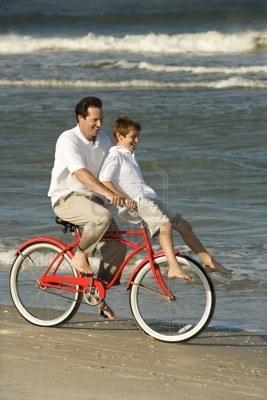 1779223 Padre Montar Bicicleta En La Playa Con Pre Adolescente Hijo En El Manillar