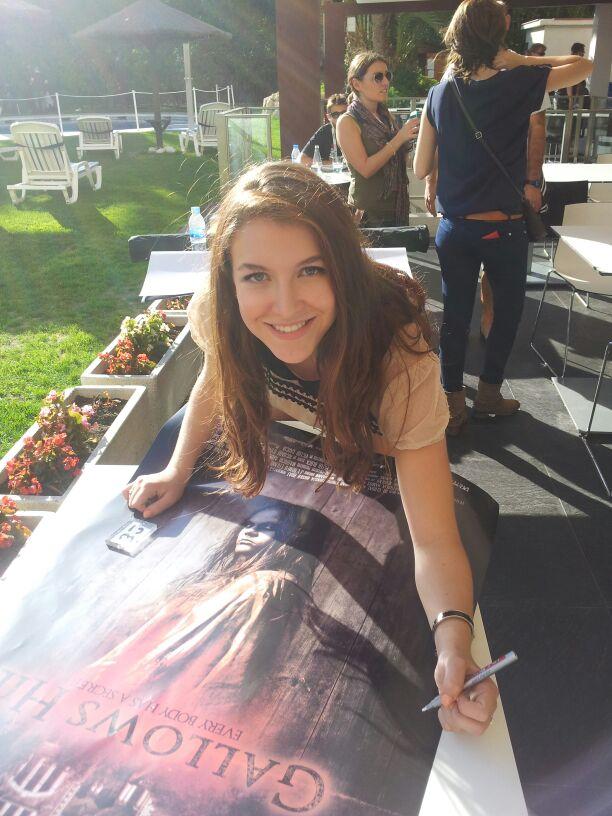 Nathalia Ramos firmando un póster de Gallows Hill
