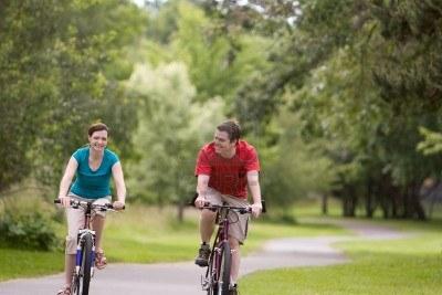 3338780 Una Joven Pareja Sus Bicicletas De Paseo En Un Parque Sendero Sonriendo El Hombre Se Ve Sobre La Muj