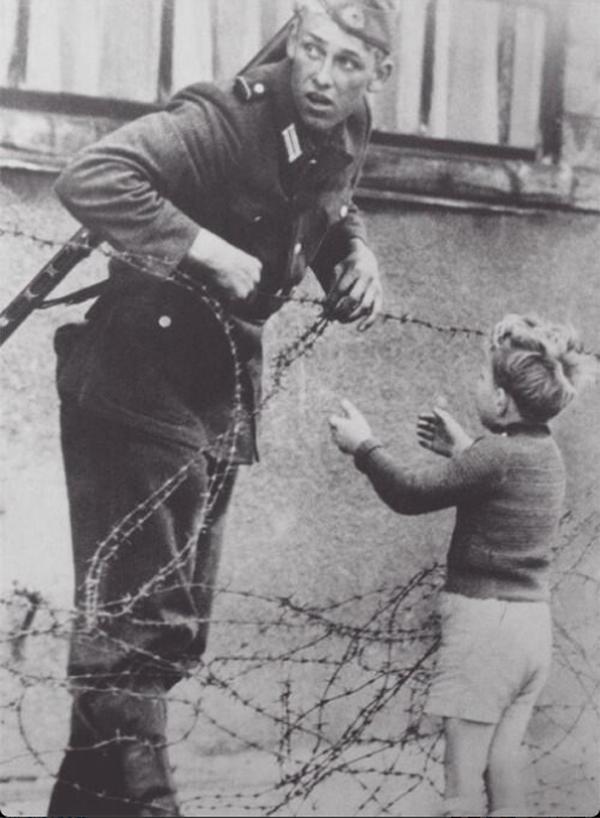 7. Soldado ayudando a un niño a cruzar el muro de Berlín
